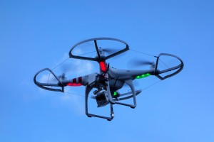 DW0D7X Miniature drone / unmanned aerial vehicle / UAV equipped with camera in flight against blue sky with clouds