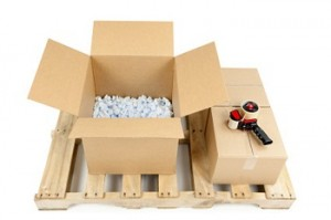 Shipping pallet with one new open cardboard box half full of packing peanuts, and two closed boxes with a tape gun. Isolated on white.